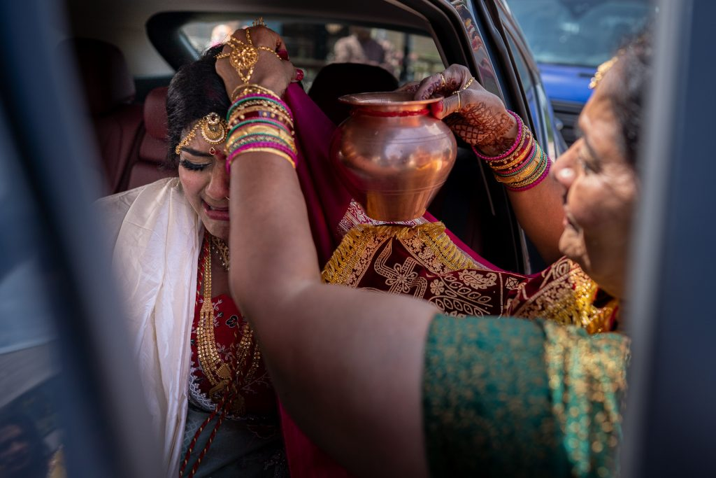 bride crying while her mom pour water on her head