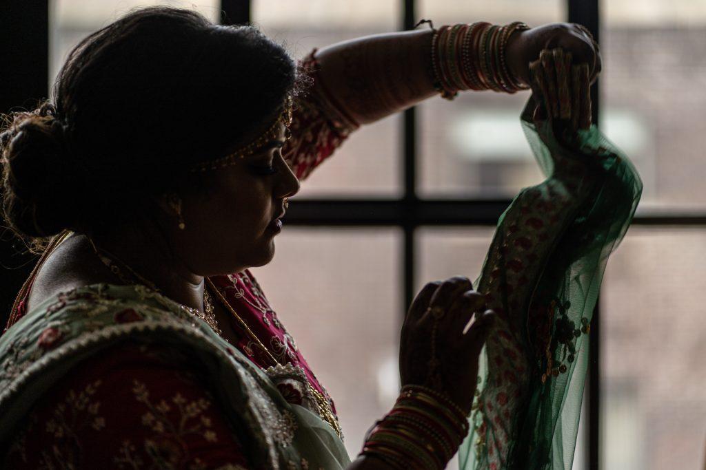 bride helping bridesmaid getting ready