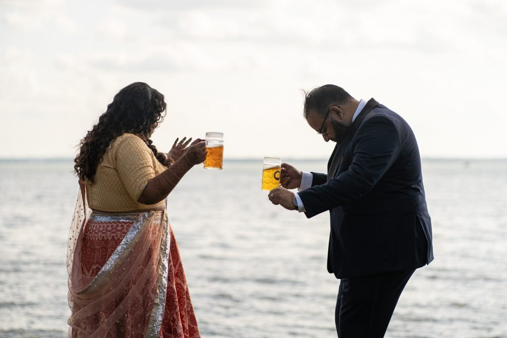 couple dancing by the lake with beers on their hands