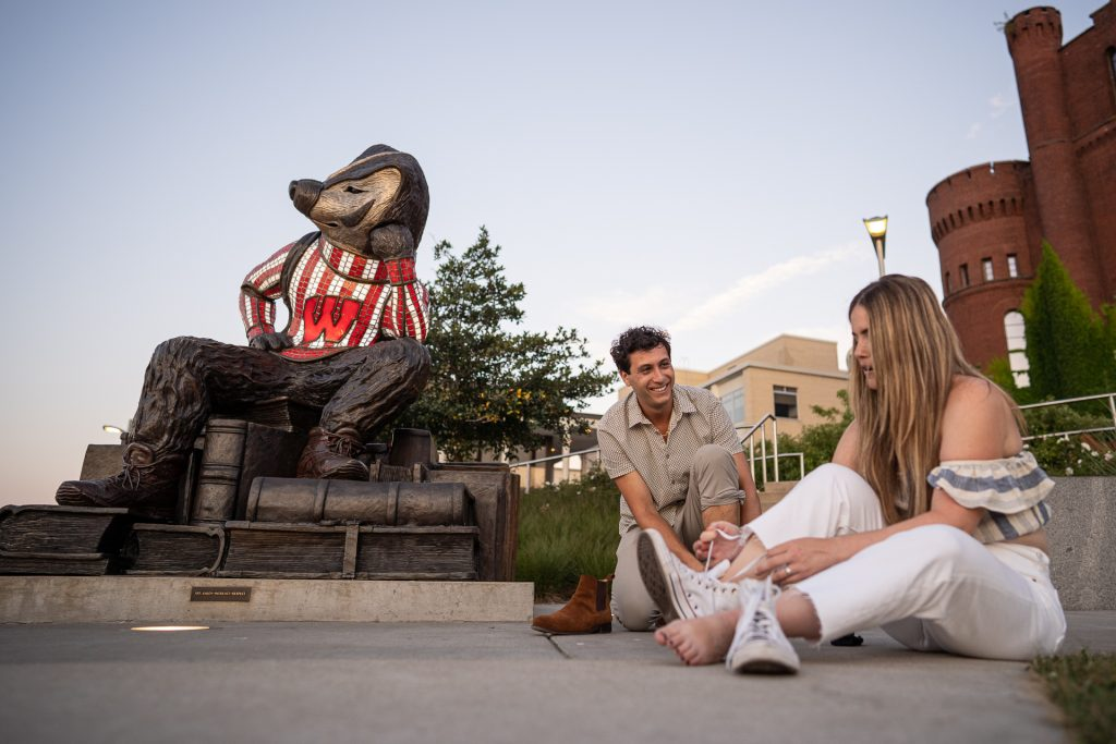 couple putting on shoes by uw madison mascot