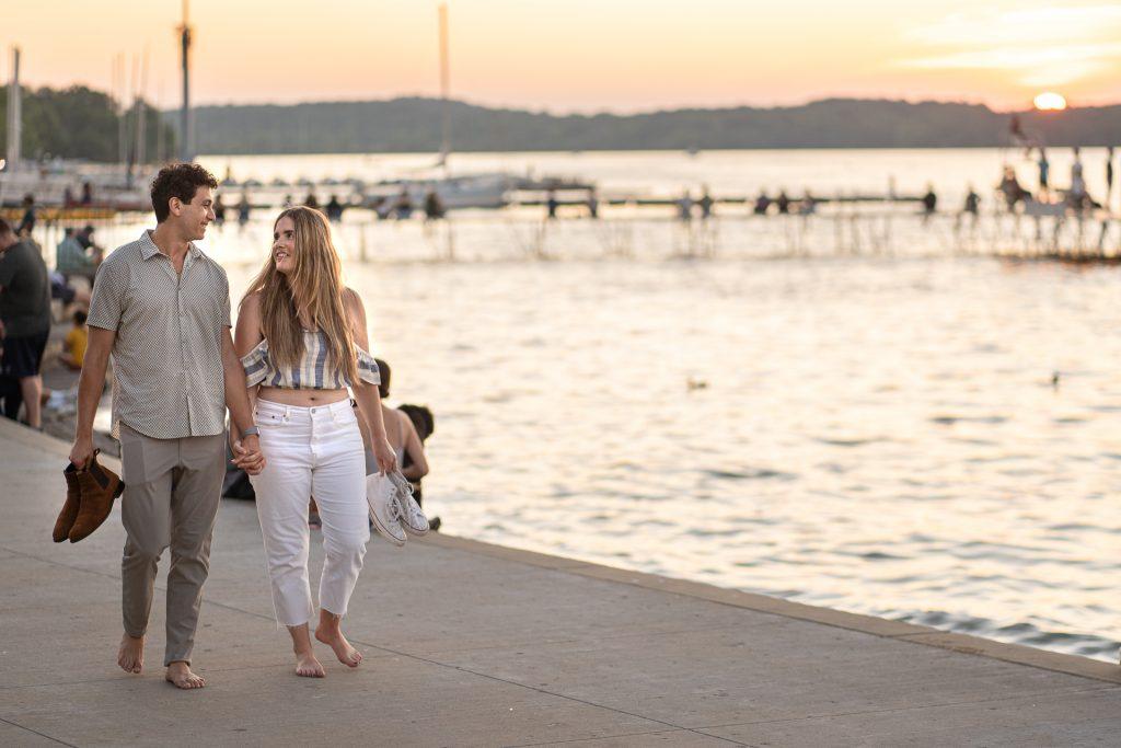 couple walking barefoot by lake mendota