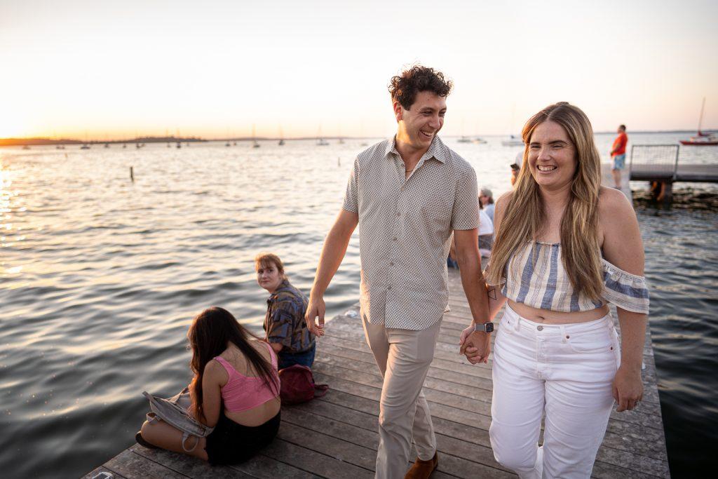 engaged couple walking on UW goodspeed family pier