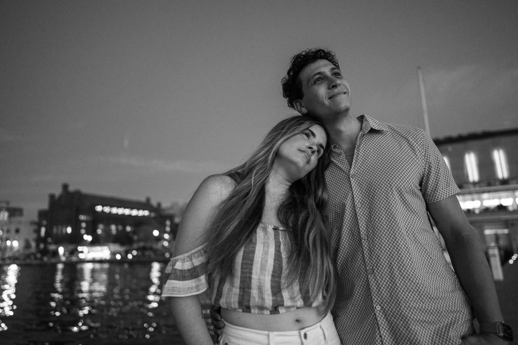 engaged couple watching sunset at lake mendota