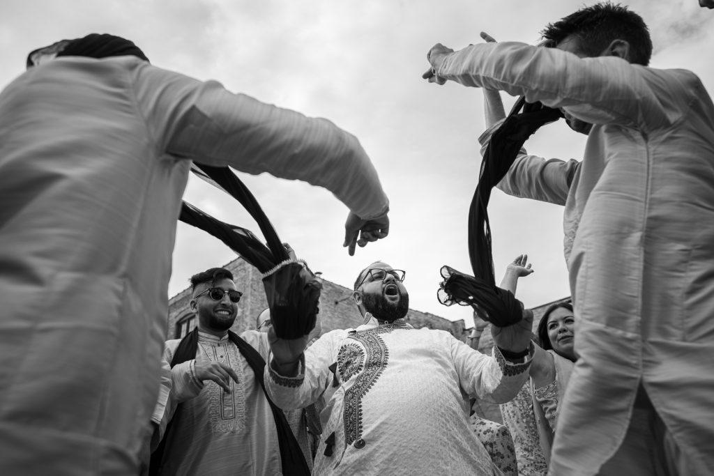 groom dancing holding groomsmen scarfs