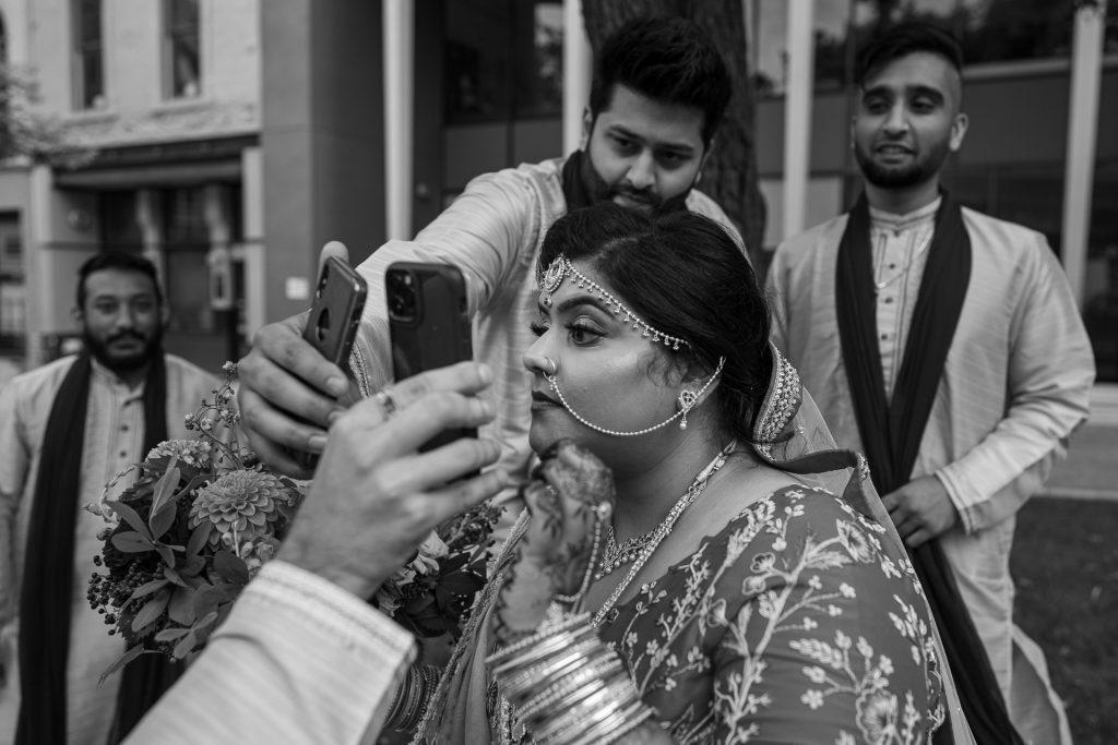 groomsmen helping bride check herself on cellphone camera
