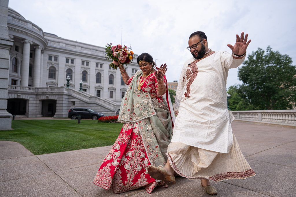 indian couple skipping in front of wisconsin state capitol