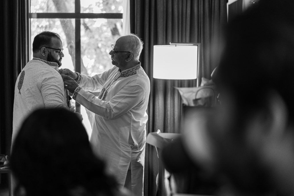 indian groom getting ready with his dads help
