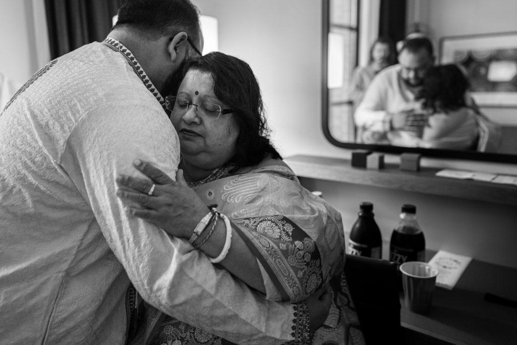 mom hugging groom before wedding ceremony