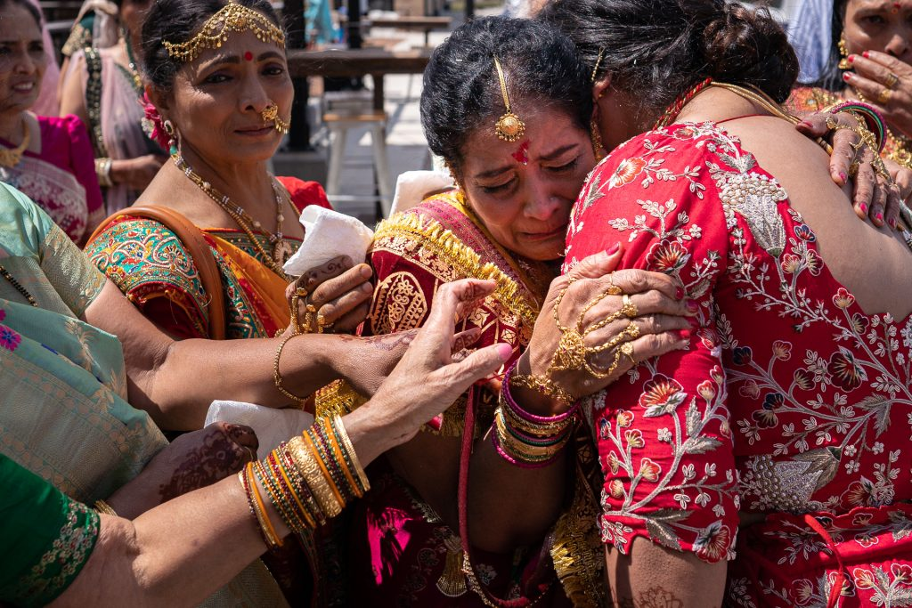 mother of the bride crying and hugging bride