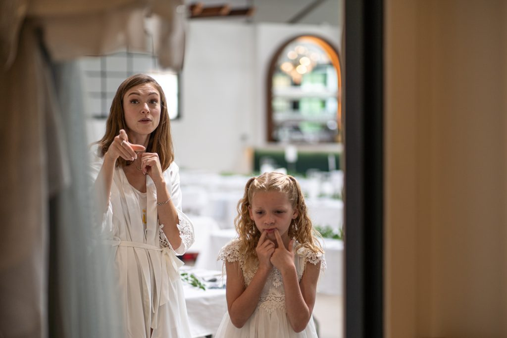bride and flower girl looking at their dresses