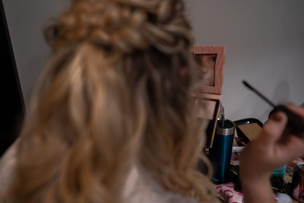 bridesmaid doing makeup reflection