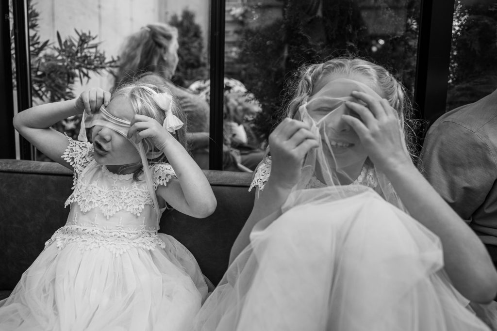 flower girls playing with their veils