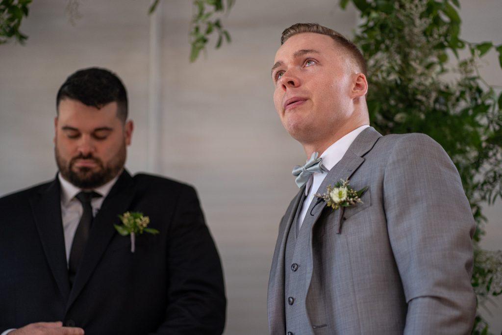 groom breathing deep while bride walks down the aisle
