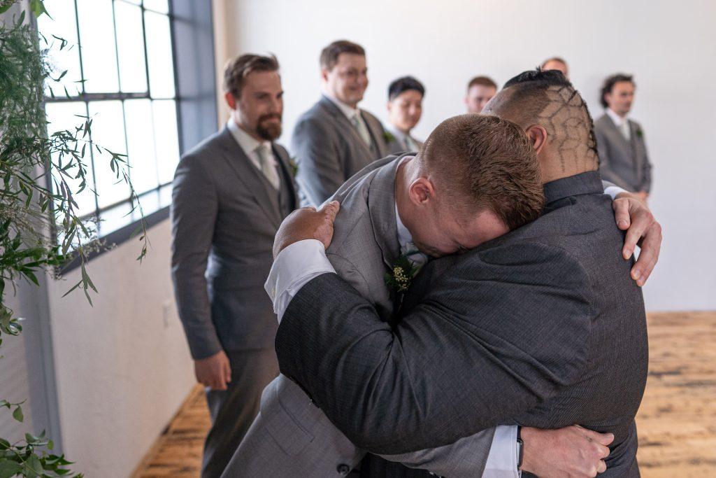 groom hugging best man wedding ceremony